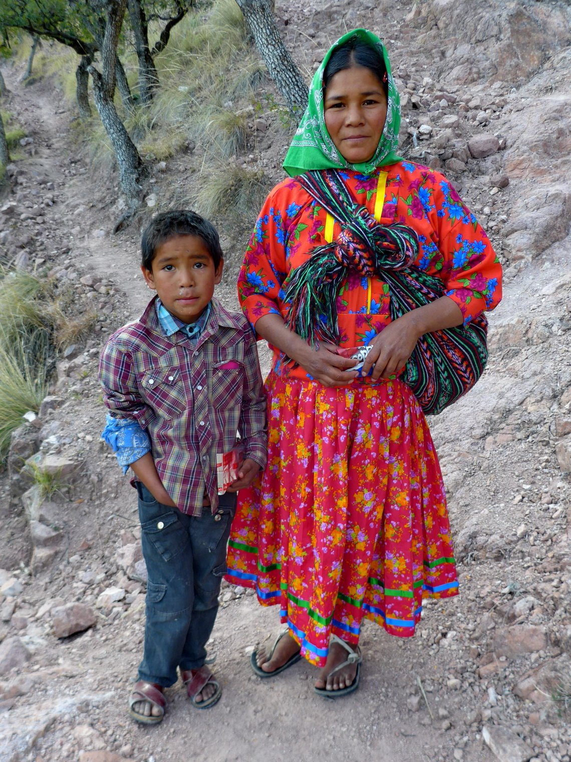 Tarahumara boy with his mother who wears a traditional costume