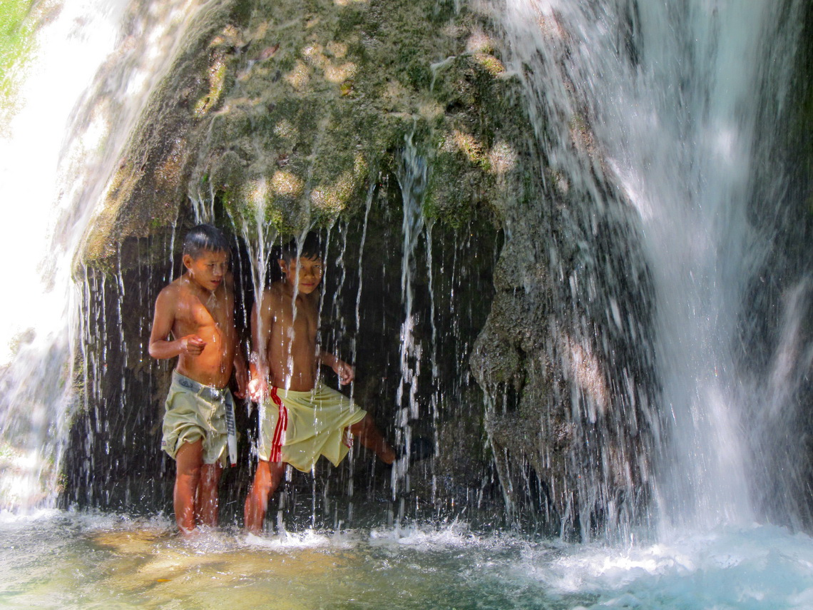 Two boys from Unini with the cave behind the waterfall