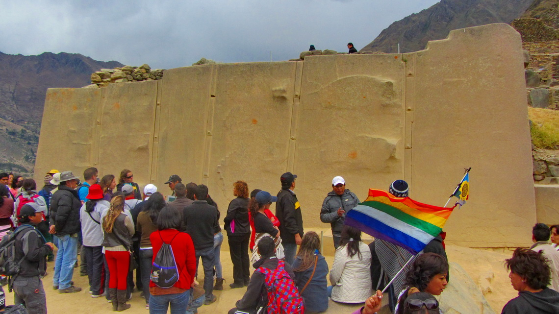 Wall in Ollantaytambo made by huge stones, the rainbow flag of the Quechua and a lot of tourists