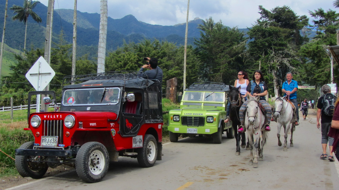 Willys, the most popular car in Colombia on the left with riding tourists on the right